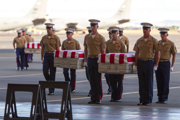 U.S. Marines carry the remains of 36 unidentified Marines found at a World War II battlefield during a ceremony at Joint Base Pearl Harbor-Hickam, Sunday, July 26, 2015, in Honolulu. (AP Photo/Marco Garcia)