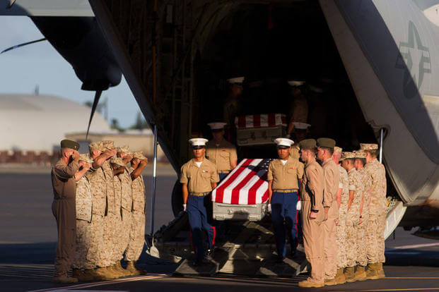 U.S. Marines unload the remains of 36 unidentified Marines found at a World War II battlefield during a ceremony at Joint Base Pearl Harbor-Hickam, Sunday, July 26, 2015, in Honolulu. (AP Photo/Marco Garcia)