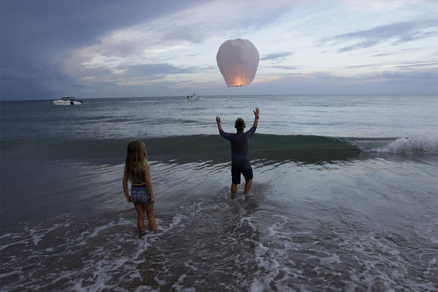 Andrew Grubowski, 10, of Palm City, Fla., releases a lantern during a vigil for Austin Stephanos and Perry Cohen, Tuesday, July 28, 2015, in Stuart, Fla. (AP Photo/Lynne Sladky)