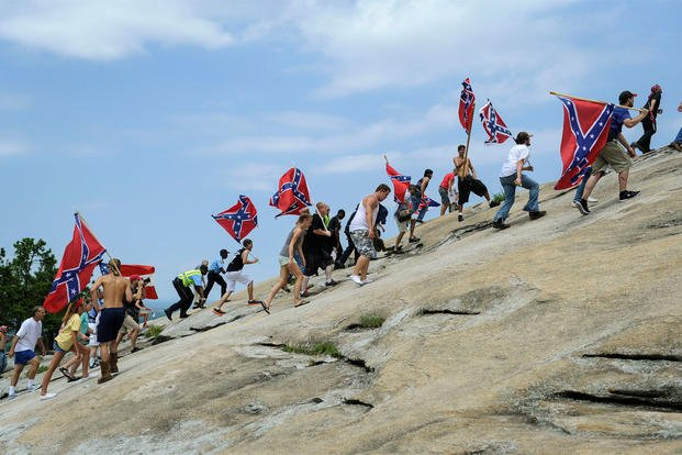 Confederate flag supporters climb Stone Mountain to protest of what they believe is an attack on their Southern heritage during a rally at Stone Mountain Park in Stone Mountain, Ga., on Saturday, Aug. 1, 2015.