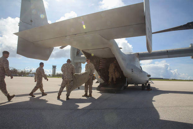 U.S. Marines move water bladders out of an MV-22B Osprey at Saipan International Airport, Saipan, Aug. 9, 2015. (U.S. Marine Corps photo by Cpl. Ryan C. Mains)