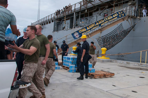 Sailors and Marines load cases of water onto the amphibious dock landing ship USS Ashland (LSD 48) in preparation for the ship getting underway to deploy to Saipan. (U.S. Navy photo by Leah Eclavea/Released)