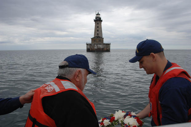 Former Coast Guard member Walter Scobie and Petty Officer 1st Class Christopher Connolly prepare to lay a wreath in Lake Superior near the Stannard Rock Lighthouse, June 17, 2015. (U.S. Coast Guard photo by Senior Chief Alan Haraf)