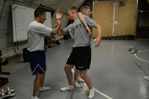 U.S. Air Force Tech Sgt. Roman-Rivera teaches combative moves to U.S. Army Spcs. Cameron Hicks and Cody Hougnon, Aug. 25, 2015, at Bagram Airfield, Afghanistan. (U.S. Air Force photo by Senior Airman Cierra Presentado)