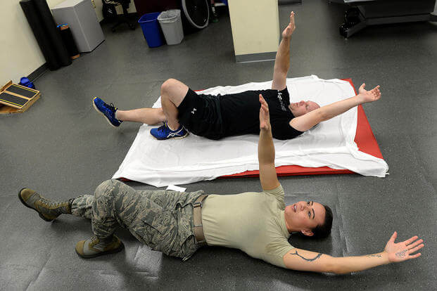 Staff Sgt. Amber Coley, a physical therapy technician, demonstrates an exercise for Tech. Sgt. Jared Rhynehart during a rehabilitation session, Nov. 18, 2015, at Seymour Johnson Air Force Base, N.C. (Photo: Airman 1st Class Ashley Williamson)