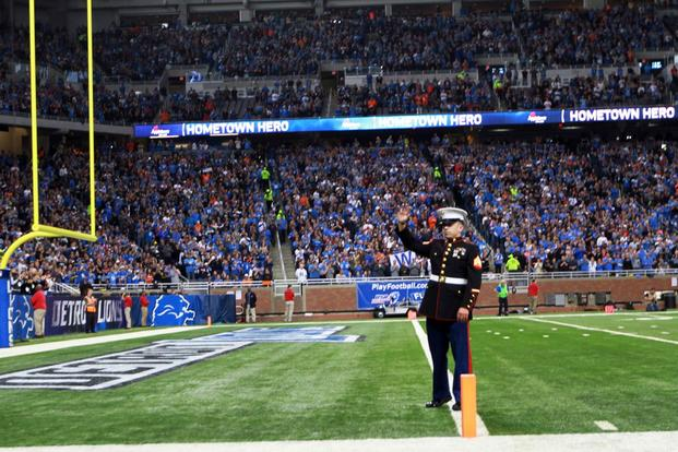 U.S. Marine Corps Sgt. Benjamin J. Annarino waves to more than 60,000 cheering fans during a Detroit Lions football game at Ford Field in Detroit, Oct. 20, 2015. (Photo by: Sgt. J. R. Heins)