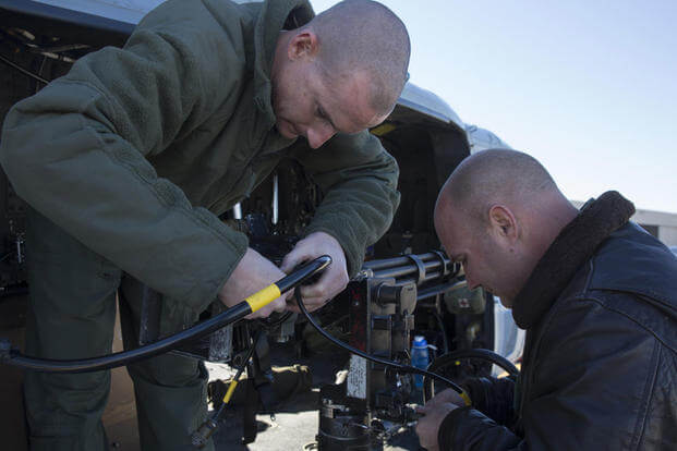 Two combat marksmanship trainer instructors prepare an M134 GAU-17 Minigun prior to a formation flight and aerial gunnery shoot at Marine Corps Air Station Camp Pendleton, California, Dec. 17. (Photo: Sgt. Lillian Stephens)