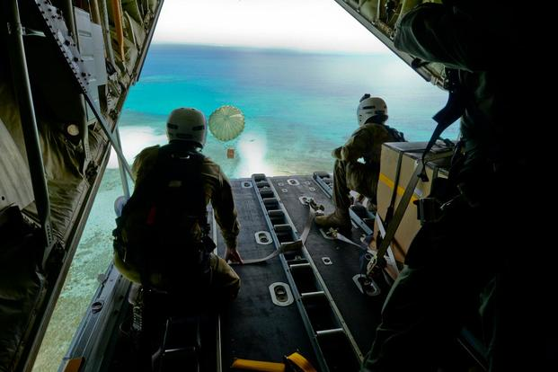 Australian Army Cpl. Teome Matamua and Sgt. Phillip McIllvaney, 176th Air Dispatch Squadron loadmasters, deliver the first bundle of Operation Christmas Drop 2015 to the island of Mogmog, Dec. 8, 2015. (Photo: Staff Sgt. Katrina Brisbin)