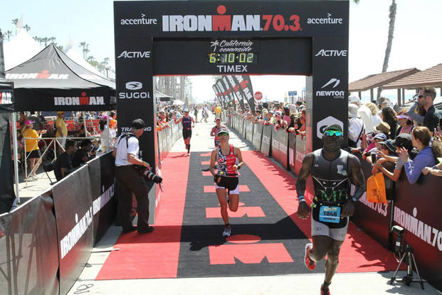 Marine Corps Staff Sgt. Kenneth Bell, right, finishes the 2015 Ironman 70.3 SuperFrog triathlon event in Coronado, Calif., Sept. 27, 2015. (Photo: U.S. Department of Defense)