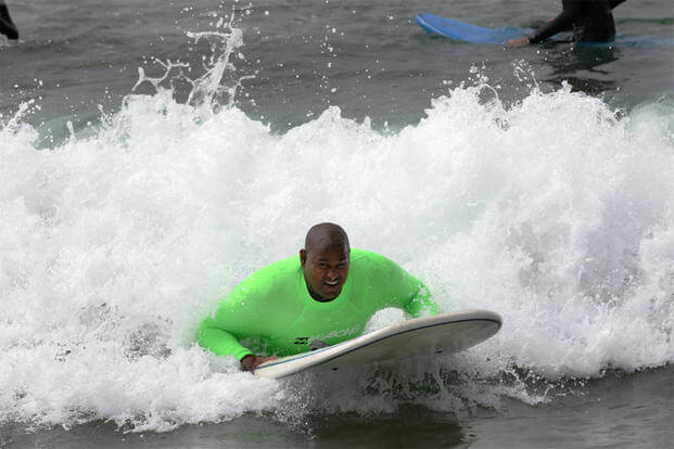 Cpl. Toran Gaal, a double amputee, rides a wave during the Operation Amped surf clinic at San Onofre beach here, Aug. 24, 2013. (Photo: Cpl. Michael Iams)