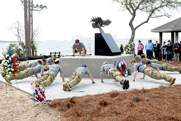 Marines, led by Raider Nathan Harris, do some ceremonial push-ups at the memorial dedicated to the Raider 7. (Photo: Katie Lange)