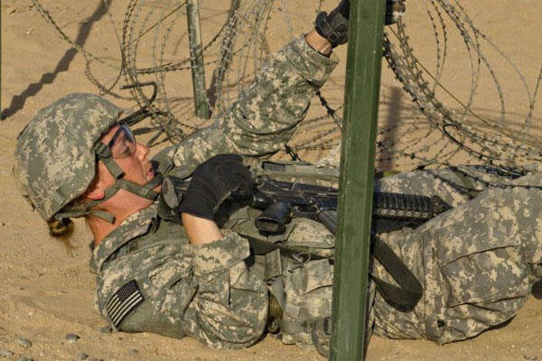 Major Erin C. Robinson, a medical plans and operations officer with U.S. Army Central, negotiates a wired obstacle during Expert Medical Badge Testing Oct. 15, 2013 on Camp Buehring, Kuwait. (Photo by Sgt. Adam C. Keith, U.S. Army Central)