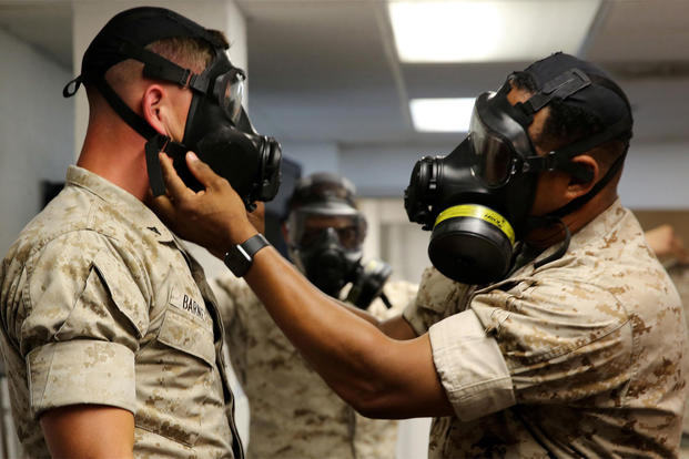 Sgt. Maj. Brian Taylor checks the M53 Chemical-Biological Protective Mask of Lance Cpl. John N. Barnett during gas mask drills on June 7. (Photo: Lance Cpl. Maverick Mejia)