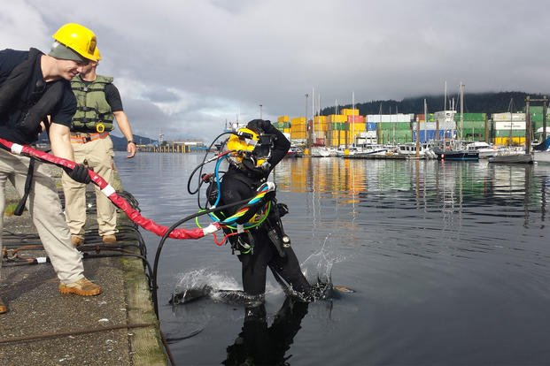 A 7th Engineer Dive Detachment Soldier conducts a front step entry into the Alaskan water during a two-month long breakwater repair project that concluded Oct. 18, in Ketchikan, Alaska. (U.S. Army photo/7th Engineer Dive Detachment)