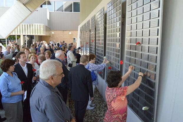 Attendees place flowers on their loved ones plates at the Legacy Data Plate Wall of Honor Tribute Ceremony at the National Museum of the U.S. Air Force, May 2014. (Photo courtesy of Air Force Museum Foundation)