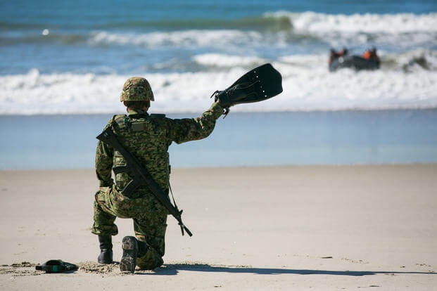 A Japan Ground Self-Defense Force soldier signals a landing location for JGSDF soldiers out at sea on Combat Rubber Raiding Crafts during Exercise Iron Fist 2016 aboard Camp Pendleton, Feb. 2, 2016. (U.S. Marine Corps/Cpl. Xzavior T. McNeal)