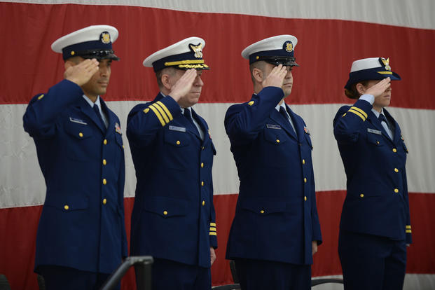 Coast Guard Air Station Cape Cod crewmembers salute during the playing of the national anthem, Monday, June 19, 2017, in Cape Cod. (U.S. Coast Guard photo/Petty Officer 3rd Class Andrew Barresi)