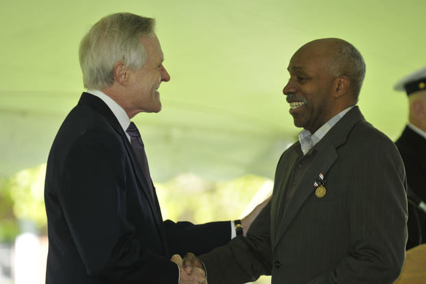 Ray Mabus congratulates Clinton Lee Suggs following an April 24, 2015 medal presentation where Suggs received the Prisoner of War Medal at the Fort McNair portion of Joint Base Myer-Henderson Hall. (Joint Base Myer-Henderson Hall PAO/Jim Dresbach)