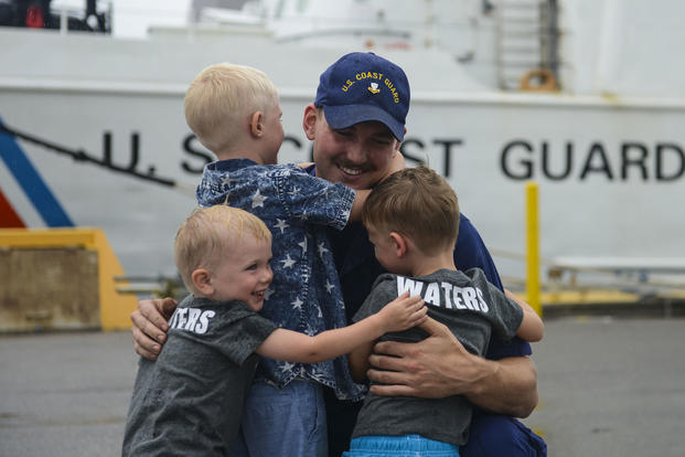 A crewmember from Coast Guard Cutter Valiant hugs his children Tuesday, June 6, 2017, in Mayport, Florida. (U.S. Coast Guard photo/Petty Officer 2nd Class Anthony L. Soto)