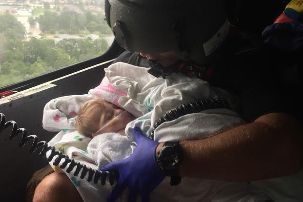 A Coast Guard aircrew assists infant during the aftermath of Hurricane Harvey in the greater Houston Metro Area Aug. 29, 2017. (U.S. Coast Guard photo/Petty Officer 2nd Class Chase Redditt)