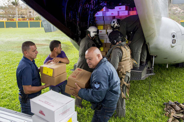 Marines assigned to Marine Medium Tiltrotor Squadron 162, embarked aboard the amphibious assault ship USS Kearsarge, and local volunteers unload food from an MV-22 Osprey in Jayuya, Puerto Rico, Sept. 27, 2017. (U.S. Navy photo/Ryre Arciaga)