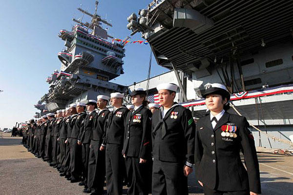 The crew of the USS Enterprise stands at attention after disembarking the ship during the inactivation ceremony for the first nuclear-powered aircraft carrier USS Enterprise at Norfolk Naval Station on Dec. 1, 2012.