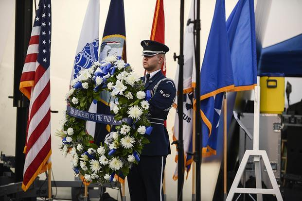 An Airman presents the wreath used in a wreath-laying ceremony. (Air Force photo/Tech. Sgt. Joshua L. DeMotts)