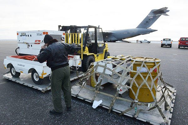 Coast Guard Chief Warrant Officer Samuel Pulliam and SSgt Peyton Wackerman of the Alaska Air National Guard prepare equipment for transport while demobilizing a Forward Operating Location in Deadhorse. (U.S. Coast Guard/PO1 Shawn Eggert)