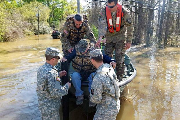 Soldiers help a flood victim from a special rescue boat in Ponchatoula, La., March 13, 2016. The soldiers are assigned to the Louisiana National Guard's 2225th Multi-Role Bridge Company. (Louisiana National Guard/1LT Rebekah Malone)