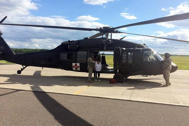 Crewmembers from the Wisconsin Army National Guard's Company F assist a dialysis patient from the Bad River Reservation in northern Wisconsin out of a UH-60 Black Hawk helicopter July 13, 2016. (Wisconsin National Guard photo)