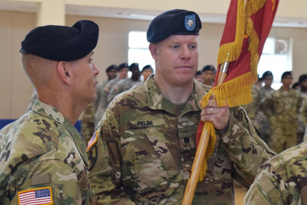 Lt. Col. Marc Pelini receives the 6th Battalion, 52nd Air Defense Artillery Regiment colors from Col. Mark Holler, 35th ADA Brigade commander, during a change of command ceremony at Suwon Air Base, South Korea, July 7. (U.S. Army/Capt. Jonathon Daniell)