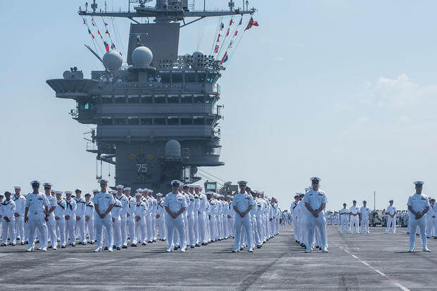 Sailors prepare to man the rails aboard the aircraft carrier USS Harry S. Truman (CVN 75) as it returns to homeport at Naval Station Norfolk, completing an 8-month deployment. (U.S. Navy/MC3 Adelola Tinubu/Released)