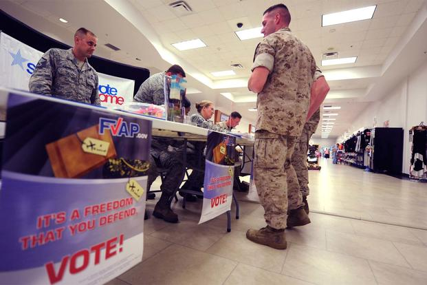 A U.S. Air Force voting officer and a Marine Corps Base assistant voting officer host a joint information booth on Oct. 21,2014, inside the Kadena Exchange, Okinawa, Japan. (USAF Photo: Stephen G. Eigel)