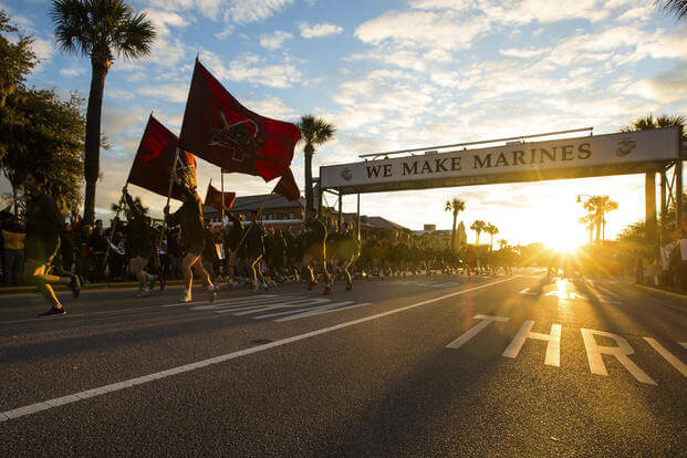 "New Marines run under the iconic ""We Make Marines"" sign during a traditional motivational run through the streets of Parris Island, S.C., on July 15, 2016. Lance Cpl. Aaron Bolser/Marine Corps"