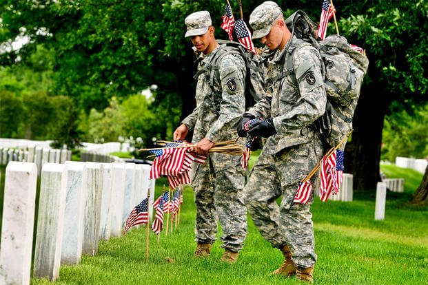 3d U.S. Infantry Regiment soldiers place American flags in front of graves at Arlington National Cemetery. (Photo Credit: 3d U.S. Infantry Regiment)