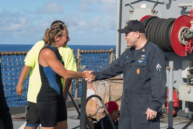 USS Ashland Command Master Chief Gary Wise welcomes aboard Jennifer Appel, an American mariner who had received assistance from Ashland crew members. (U.S. Navy/Mass Communication Specialist 3rd Class Jonathan Clay)