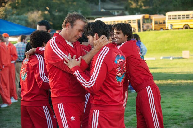 "In this image released by Disney, Kevin Costner, foreground left, embraces Carlos Pratts in a scene from ""McFarland, USA."" (AP Photo/Disney, Ron Phillips)"