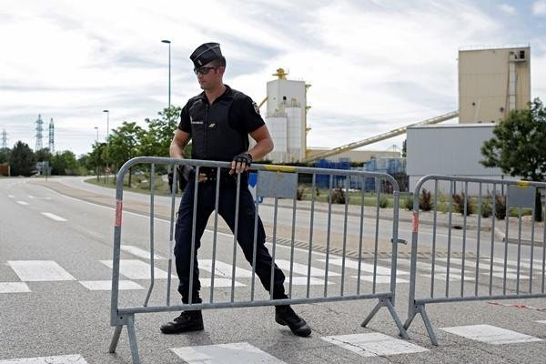A police officer blocks the road leading to a plant where a terorist attack took place, Friday, June 26, 2015 in Saint-Quentin-Fallavier, southeast of Lyon, France. (AP Photo/Laurent Cipriani)