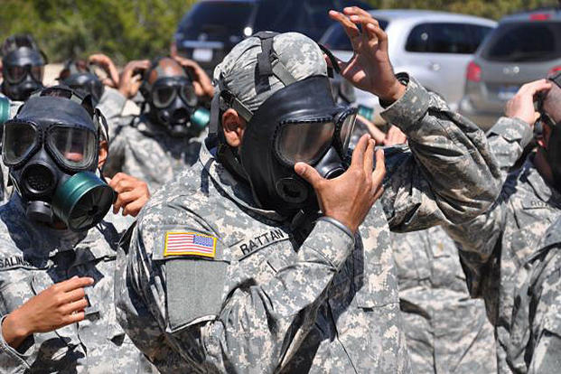 Capt. (Dr.) Tejdeep Singh Rattan, a Sikh dentist serving in the U.S. Army, checks the seal on his gas mask before entering the gas chamber during nuclear, biological and chemical training in 2010. Steve Elliott/Army