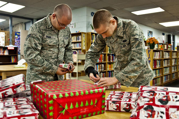 Senior Airman Adam Phair and Airman 1st Class Charles McClung, of the 46th Operations Group, finish wrapping gifts