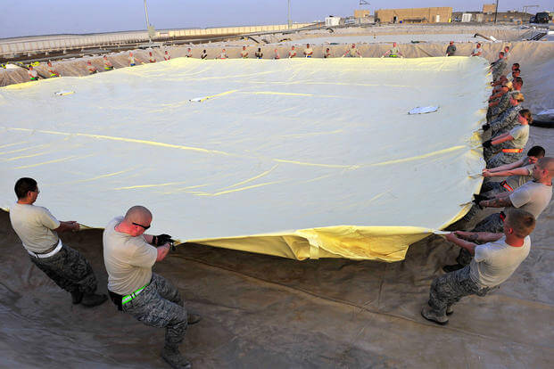 Airmen of the 380th Air Expeditionary Logistics Readiness Squadron arrange a 200,000-gallon fuel bladder at an undisclosed location in Southwest Asia, April 4, 2013. (US Air Force photo/Christina Styer)
