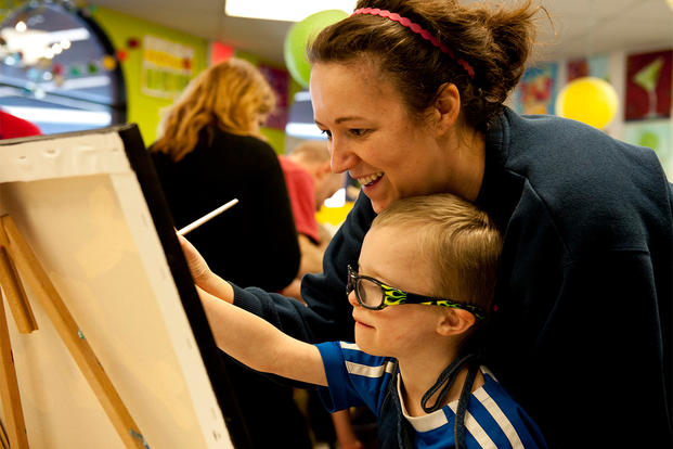 A mother and son paint during a Exceptional Family Members Program (EFMP) event at Peterson Air Force Base, Colorado. (Photo: U.S. Air Force/Senior Airman Tiffany DeNault.)