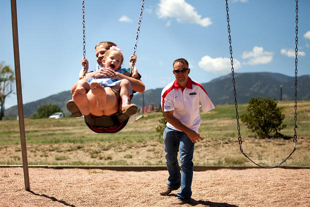 A former Marine pushes his wife and daughter on a swing. (Photo: U.S. Marine Corps/Lance Cpl. Chelsea Flowers)