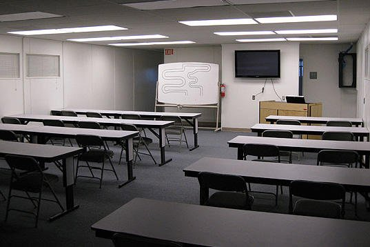 Empty room with desks, a podium and a whiteboard.