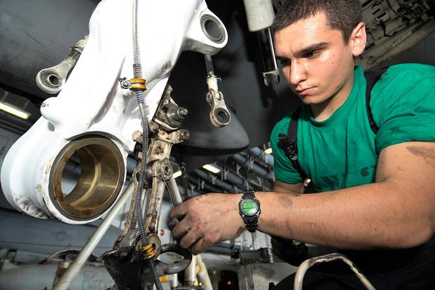 Aviation Structural Mechanic 3rd Class Donald Elder replaces an axle lever on the landing gear of an F/A-18C Hornet aboard the aircraft carrier USS Harry S. Truman. (U.S. Navy/MC2 Kilho Park)