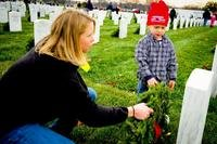 Volunteers place a wreath on a grave site during a National Wreaths Across America Day Ceremony at Arlington National Cemetery. (U.S. Air Force/Joseph Swafford)