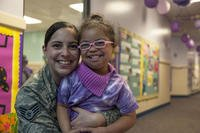 Staff Sgt. Yinell Covington, and her daughter, Maya Rosario, pose for a picture at a school parade at the Joint Base Andrews Child Development Center. (U.S. Air Force/Rustie Kramer)