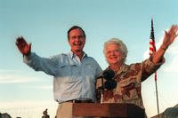 U.S. President George H.W. Bush and first lady Barbara Bush wave as they stand in the back of a vehicle during a visit to a desert encampment in Saudi Arabia, Nov. 22, 1990. The former president and his wife were paying Thanksgiving Day visits to U.S. troops in Saudi Arabia for Operation Desert Shield. (U.S. Navy photo/Ed Bailey)
