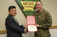 Japan- Police Chief Osamu Hamada, left, accepts a letter of appreciation from Col. Mark Coppess during an award ceremony March 8 on Marine Corps Air Station Futenma, Okinawa, Japan. (U.S. Marine Corps/Pfc. Nicole Rogge)