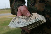 A hand holding a wad of cash. (U.S. Marine Corps photo by Sgt. Alicia R. Leaders)